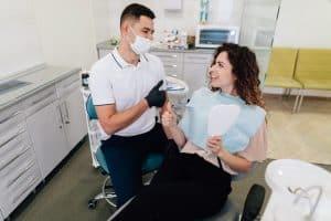 dentista com paciente em consultório odontológico