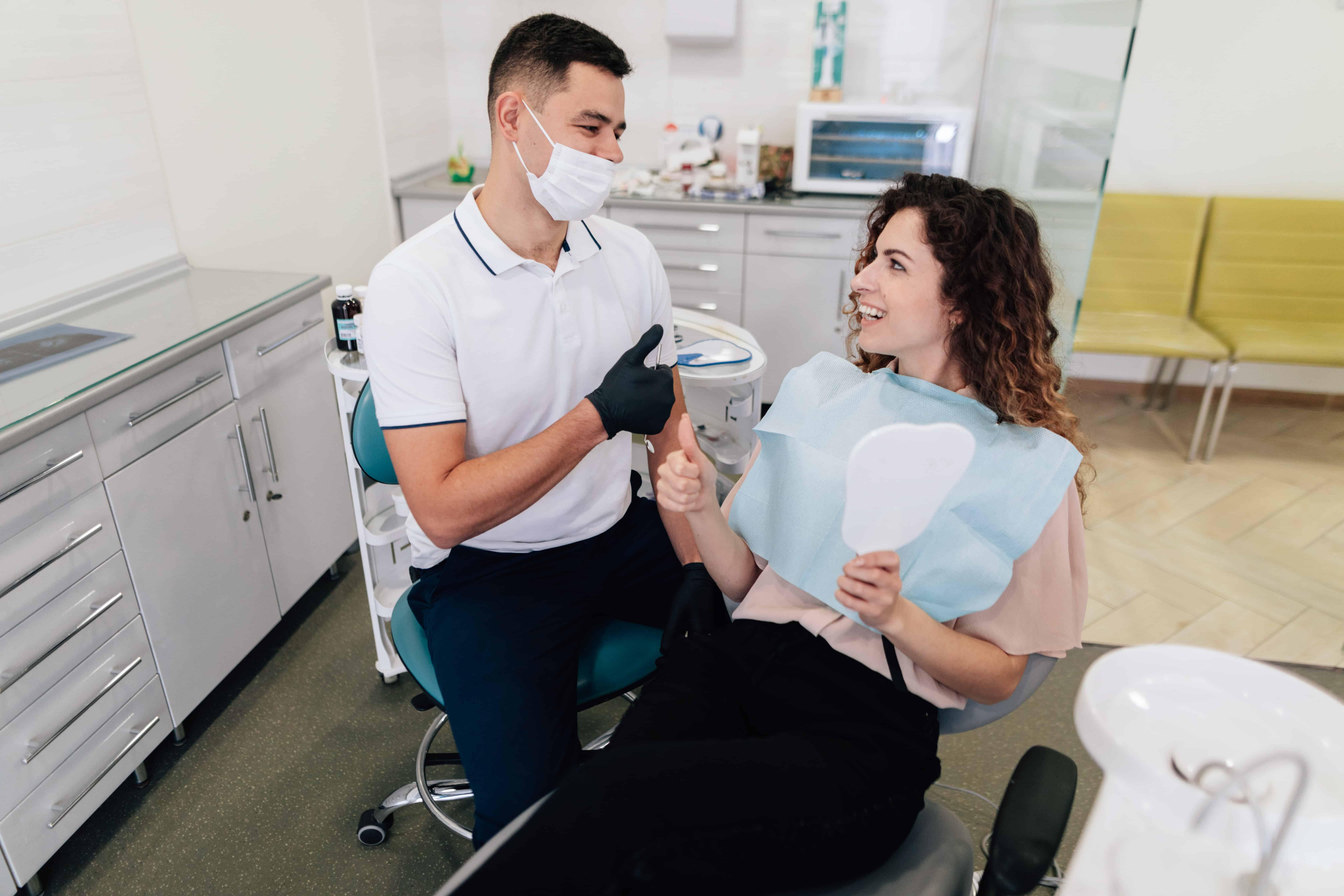 dentista com paciente sentados em caideras em consultório odontológico